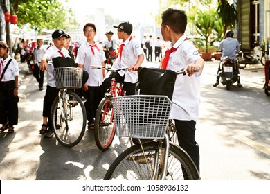 NHA TRANG, VIETNAM- MARCH 22, 2018: Vietnamese schoolboy on a bicycle turns back to his friends. Everybody at school must wear uniform with a red tie as an accessory.