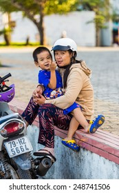 NHA TRANG, VIETNAM - SEP 30, 2014: Unidentified Vietmanese girl holds her little baby. 90% of the Vietnamese people belong to the Viet ethnic group