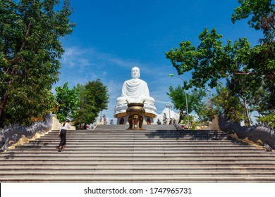 Nha Trang, Vietnam - September 10, 2018: A young woman walks to the sitting Buddha statue at the Long Son Pagoda on September 10, 2018 in Nha Trang, Vietnam