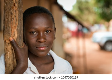 Nhacra, Republic of Guinea-Bissau - January 28, 2018: Portrait of a young african boy at the entrance of his home in the town of Nhacra in Guinea Bissau, West Africa