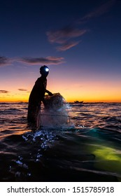 Nhan Trach commune, August 11, 2019: A high quality black silhouette of a man who is worth catching fish on the surface of the sea at dawn