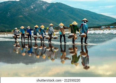 NhaTrang, Vietnam. Women carry salt from salt farm to factory.