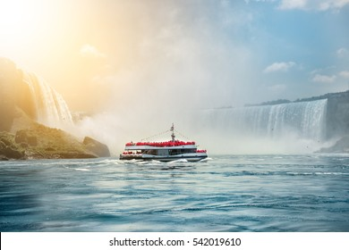 Niagara Falls boat tours attraction. Tourist people sailing on the travel boat close to the Niagara Horseshoe Fall at sunny hot summer day.