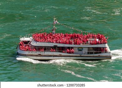 Niagara Falls, Canada - June 15, 2018: Cruiser Boat Hornblower with tourists coming fron the bottom of Horseshoe waterfall. Niagara Falls, Canada.