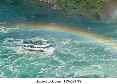 Niagara Falls, Canada and US border - July 4, 2018:  Tour boat Maid of the Mist on the Niagara River in summer under a rainbow approaching the Canadian Horseshoe Falls.