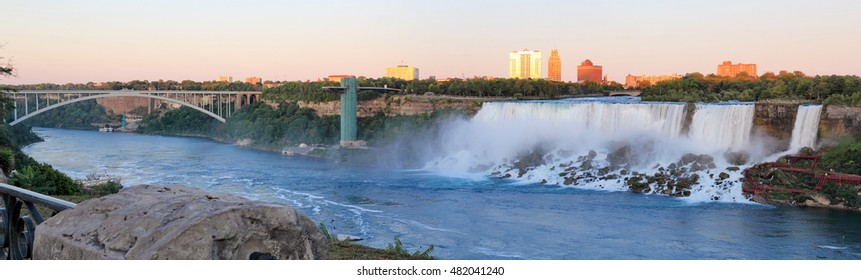 Niagara Falls Canada view of the American falls and the Niagara River at dusk, looking up to the Rainbow bridge border crossing to Niagara Falls, New York.