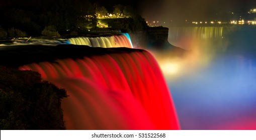 Niagara Falls lit at night show by colorful lights. American waterfall