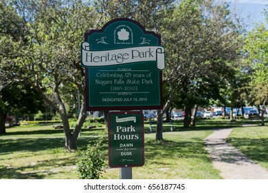 NIAGARA FALLS, NY - June 3, 2017: Heritage park sign seen at the Niagara Falls State Park on June 3, 2017 in Niagara Falls, NY, reminding visitors that park hours are from dawn to dusk.