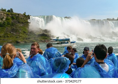 Niagara Falls, NY - September 10 2005: Group of tourists in blue raincoats watching Niagara Falls and taking pictures. At background boat Maid of Mist with tourists and waterfall.