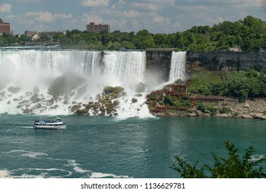 Niagara Falls, NY, USA - July 4, 2018:  View from Canadian side in summer of tourists viewing the American and Bridal Veil Falls from shore and from tour boat Maid of the Mist on the Niagara River.