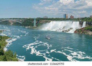 Niagara Falls, NY, USA - July 4, 2018:  Looking down Niagara River in summer at the American and Bridal Veil Falls, tour boat Maid of the Mist, and Rainbow Bridge connecting the U.S. and Canada.
