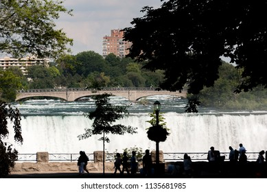 Niagara Falls, NY, USA.  Top of the American Falls in summer as viewed from a Canadian side lookout, foreground silhouettes.