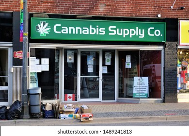 Niagara Falls, Ontario / Canada - August 11 2019: Cannabis Supply Company sign and storefront on main street in old downtown Niagara Falls Canada. Trash and recycling are out to curb store closed dark