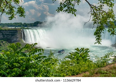 Niagara Falls, Ontario, Canada - July 4, 2018:  View of Horseshoe Falls and tour boat Maid of the Mist from Canadian side in summer, trees and vegetation in foreground.