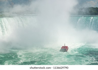 Niagara Falls, Ontario, Canada - July 4, 2018:  View from Canadian side in summer of tourists viewing the center of the Horseshoe Falls from tour boat Hornblower on the Niagara River.