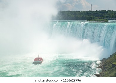 Niagara Falls, Ontario, Canada - July 4, 2018:  View from Canadian side in summer of tourists viewing the Horseshoe Falls from tour boat Hornblower on the Niagara River.