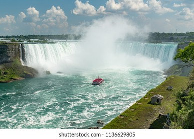 Niagara Falls, Ontario, Canada - July 4, 2018:  View from Canadian side in summer of tourists viewing the Canadian Horseshoe Falls from both ends and from tour boat Hornblower on the Niagara River.