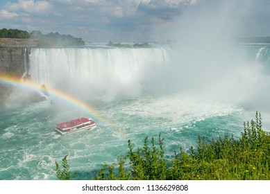 Niagara Falls, Ontario, Canada - July 4, 2018:  View from Canadian side of the Horseshoe Falls in summer and tour boat Hornblower under a rainbow on the Niagara River, vegetation in foreground.