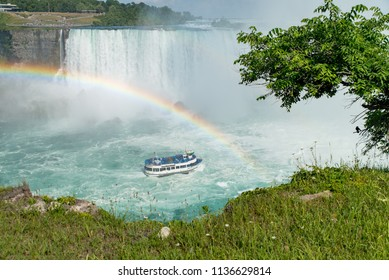 Niagara Falls, Ontario, Canada - July 4, 2018:  View of the Canadian Horseshoe Falls in summer and tour boat Maid of the Mist under a rainbow on the Niagara River, vegetation in foreground.