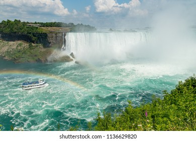 Niagara Falls, Ontario, Canada - July 4, 2018:  View from Canadian side of the Horseshoe Falls in summer and tour boat Maid of the Mist under a rainbow on the Niagara River, vegetation in foreground.