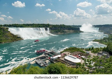 Niagara Falls, Ontario, Canada and New York State, USA - July 4, 2018:  Looking up Niagara River from Canadian side in summer; American and Bridal Veil Falls on left, Canadian Horseshoe Falls on right