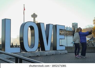 Niagara Falls, Ontario, Canada - Nov 9, 2020: Older couple taking selfie together next to love sign.