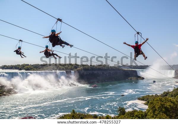NIAGARA FALLS, ONTARIO, CANADA - SEPTEMBER 4: Four people taking zipline ride at Niagara Falls in summer on Sep. 4, 2016, Ontario, Canada.  New zipline in Niagara Parks opened in the summer of 2016