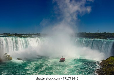 NIAGARA FALLS, ONTARIO - JUNE 2016: Panoramic View of the Canadian Falls with people boarded on a cruise ship in Ontario, Canada