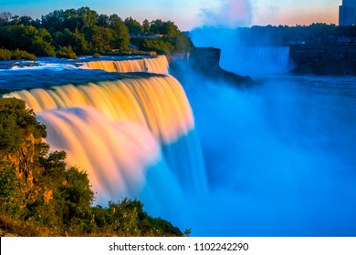 Niagara falls in the summer during beautiful evening with orange sunset lights. Water being hit by orange light. Niagara falls in the evening background. Niagara falls with orange reflection from sun.