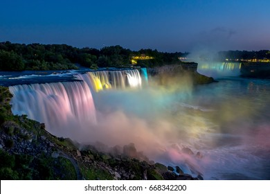 Niagara falls in the summer during beautiful evening, night with clear dark sunset blue sky. Water being hit with many colorful lights that is beautiful in a way. Sky turning dark and cold.