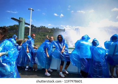Niagara Falls, USA – August 29, 2018: Happy group tourists in blue raincoats on boat tour watching Niagara Falls