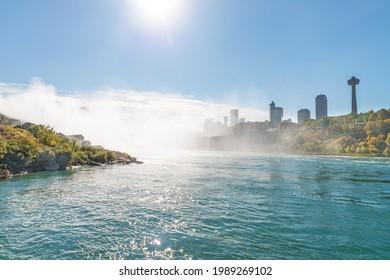 Niagara Falls, USA - October 19, 2019: Niagara Falls waterfall and city in the mist and Niagara river in a sunny autumn day