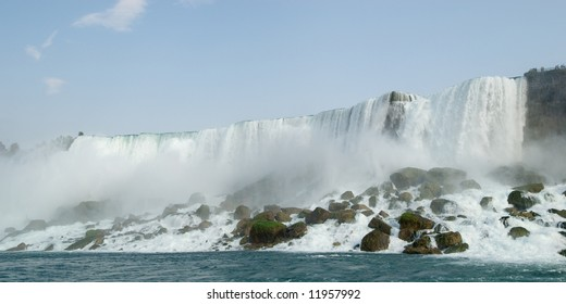 Niagara Falls view with mist and rocks at water level.