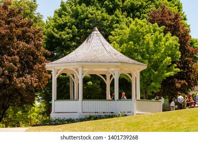 Niagara on the Lake, Ontario, Canada, June 14, 2018: White gazebo (bandstand) along  Niagara River during summer, in Queen's Royal Park, where tourists pause for a rest.