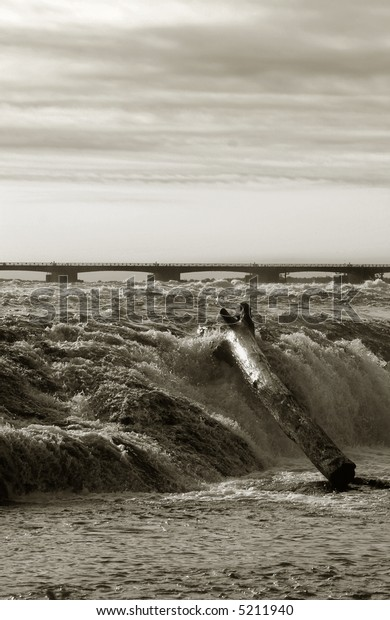 Niagara River flowing right before it becomes Niagara falls, view of rapid waves and a bridge in the distance. Sunrise