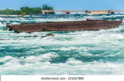 The Niagara Scow sits in the raging water of the Niagara River close to the edge of the Horseshoe Falls in Niagara Falls Canada.