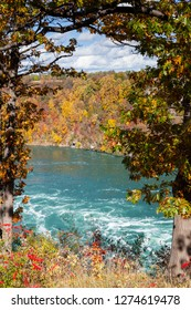 Niagara Whirlpool.  The view across Niagara Whirlpool located on the Canadian and American border.  In the background can be seen the colorful foliage of trees during the fall.