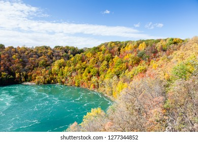 Niagara Whirlpool.  The view across Niagara located on the Canadian and American border.  In the background can be seen the colorful foliage of trees during the fall.