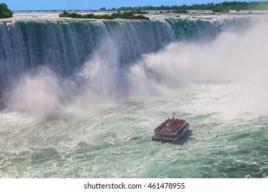 Niagara-Falls, Ontario, Canada - July 5, 2015: View of a tour boat, Hornblower, navigating near the horseshoe falls in Niagara Falls, Ontario, Canada