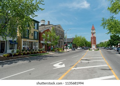Niagara-on-the-Lake, Ontario, Canada - July 5, 2018:  Queen Street looking northwest at shops and old Court House and City Hall on left, Memorial Clock Tower on right.
