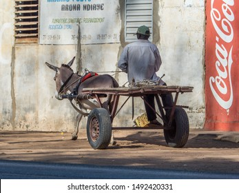 Nianing, Senegal - January 24, 2019:  Man is riding donkey cart on  the senegalese road. It is  popular transportation way in Africa