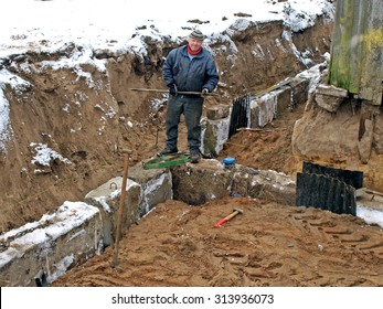 NICA, LATVIA - FEBRUARY 19, 2013: Construction worker on winter is working in foundation ditch with concrete blocks.