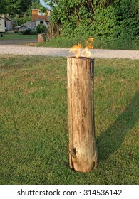 NICA, LATVIA - JUNE 23, 2013: Vertical cross sawed dry wooden log is firing as giant candle or torch on Midsummer day celebration.