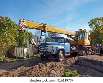 NICA, LATVIA - OCTOBER 12, 2013: Mobile crane mounted on russian truck ZIL is working to cover the new cellar with concrete panels.