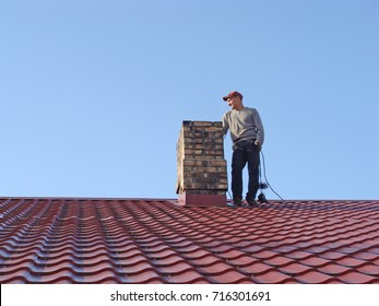 NICA, LATVIA - SEPTEMBER 16, 2017: Young man is standing on roof and sweeping chimney with metal wire brush and rope.