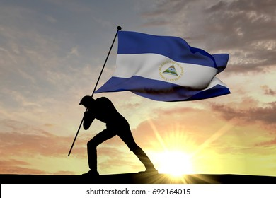 Nicaragua flag being pushed into the ground by a male silhouette. 3D Rendering
