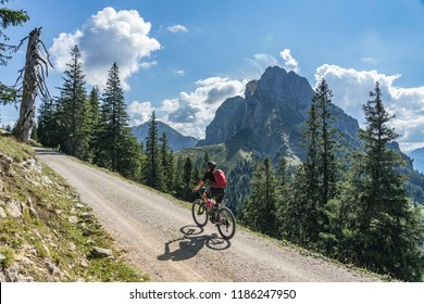 nice and active senior woman, riding her e-mountainbike in the Tannheim valley, Tirol, Austria with the village of Tannheim and famous summits Gimpel and Rote Flueh