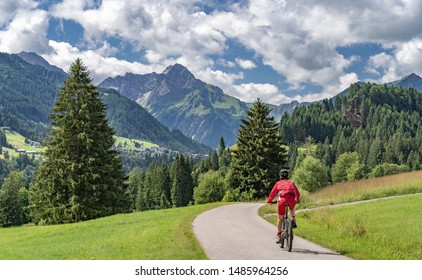nice active senior woman riding her electric mountain bike in the Kleinwalstertak, Vorarlberg, Austria, famous summit of Widderstein in the background