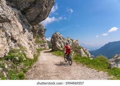 nice and active senior woman riding her electric mountainbike on the famous Tremalzo downhill from Tremalzo Pass to Riva del Garda at Garda lake, Trentino, Izaly