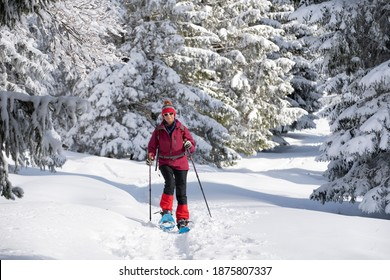 nice and active senior woman snowshoeing in deep powder snow in the Allgau alps, Bavaria, Germany